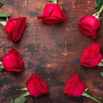 Рамка из цветов красной розы на деревянном столе поздравительная открытка дня святого валентина. квадрат.