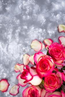 石のテーブルに赤い白いバラ花の花束のフレーム。