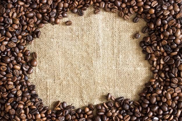 黄麻布のキャンバスに散らばっている焙煎コーヒー豆のフレーム