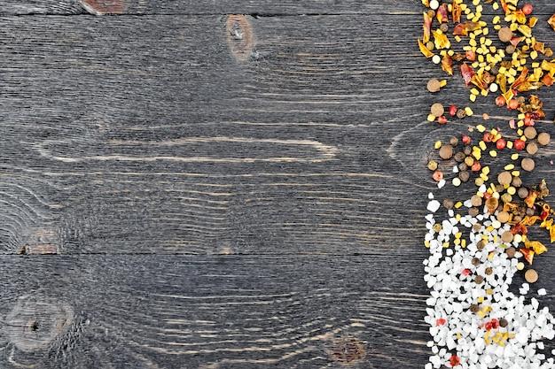 木の板の背景に塩、フェヌグリーク種子、エンドウ豆、唐辛子フレークのフレーム
