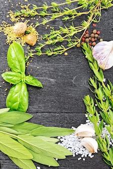 木の板の背景に香ばしい葉、バジル、セージとタイム、塩、ナツメグ、マスタードシード、コショウ、ニンニクのフレーム