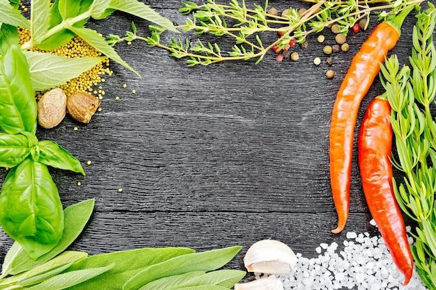 黒い木の板の背景に香ばしい葉、セージ、バジルとタイム、塩、ナツメグ、マスタードシードとニンニク、エンドウ豆と唐辛子のフレーム