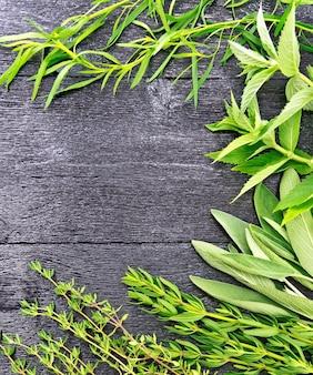 黒い木の板の背景に香ばしい葉、タラゴン、セージ、タイムのフレーム