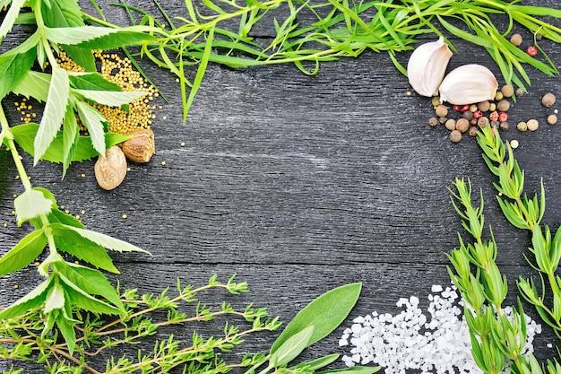 木の板の背景に香ばしい葉、タラゴン、セージとタイム、塩、ナツメグ、マスタードシード、コショウ、ニンニクのフレーム