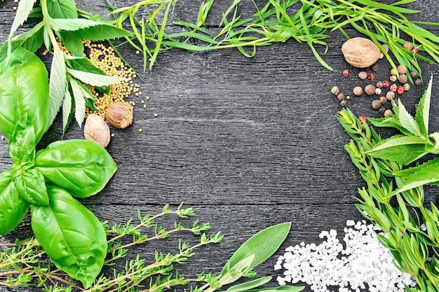 木の板の背景に香ばしい葉、タラゴン、セージ、バジルとタイム、塩、ナツメグ、マスタードシード、コショウのフレーム