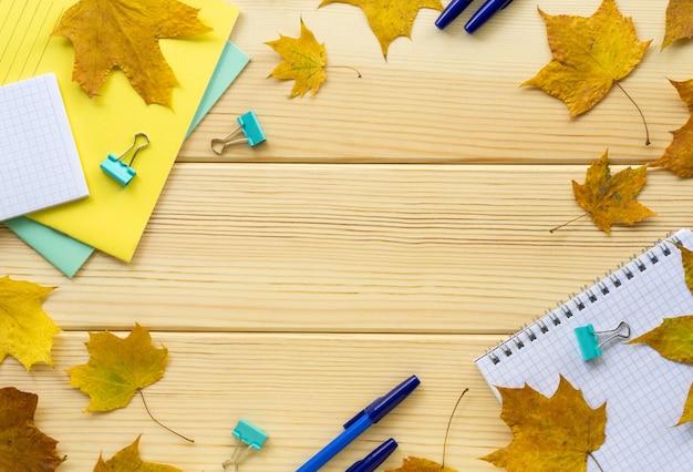 明るい木製の背景にカエデの葉と学校やオフィスの文房具のフレーム。テキスト用のスペース。