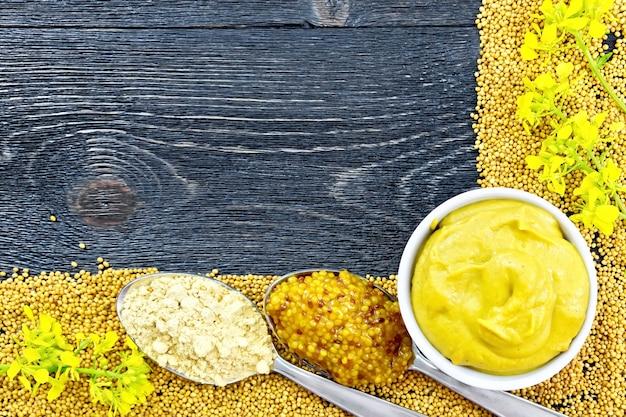 マスタードの種と花のフレーム、ボウルにマスタードソース、黒い木の板の背景にスプーンで粒状ソースと粉末