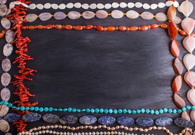 Рамка из полудрагоценных каменных бус на черной поверхности