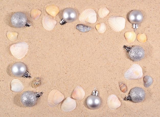ビーチの砂の上の銀のクリスマスの装飾と貝殻のフレーム