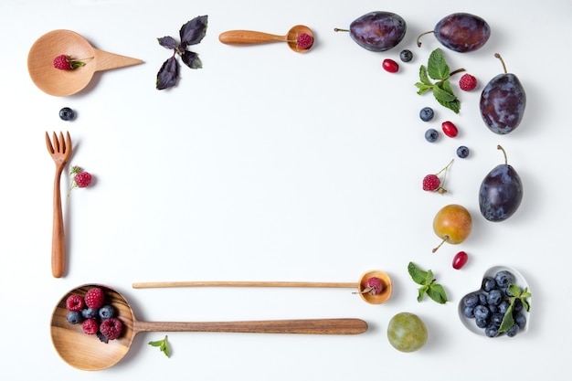 Рамка из ложек с ягодами и сливами