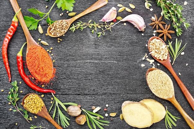 挽いたコショウ、フェヌグリーク、生姜、コリアンダー、ローズマリーの小枝、タイム、パセリ、唐辛子のさや、カルダモン、アニス、ナツメグ、ニンニクを黒い木の板の上に背景に置いたスプーンのフレーム