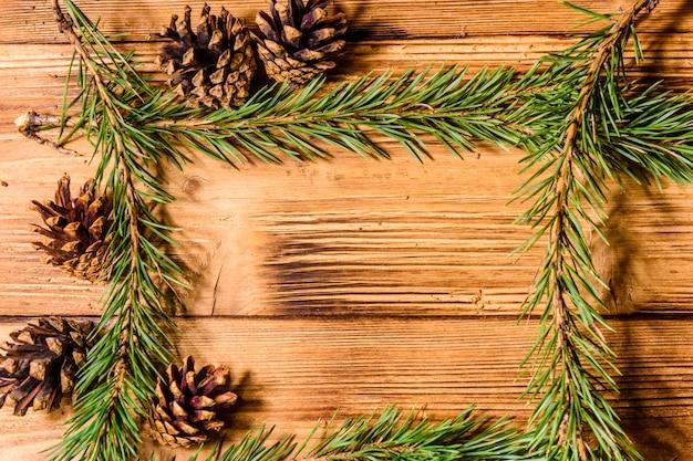 素朴な木製のテーブルの上のモミの木の枝のフレーム