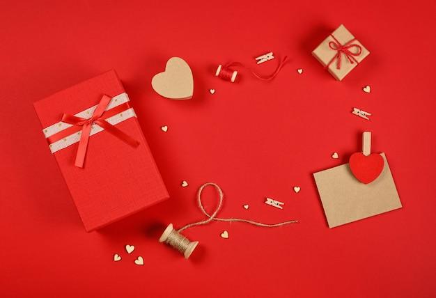발렌타인 선물, 빨간색 giftbox, 하트, 꼬기, 빨래 집게 및 빨간색 배경에 갈색 종이 카드의 프레임, 바로 위에 평평한 평신도, 높은 평면도를 닫습니다.