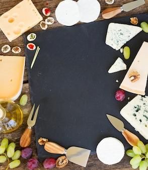 コピースペース、上面図の黒いまな板上のさまざまな種類のチーズと前菜のフレーム