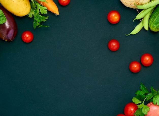 Рама из различных овощей на темном фоне, вид сверху.