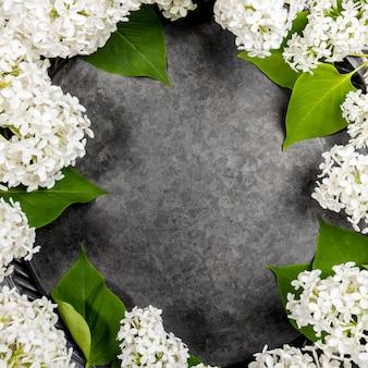 Рамка из белой цветущей сирени вокруг серой металлической тарелки в центре. макет готового блюда, рецепта или текста для весеннего праздника. вид сверху. скопируйте пространство.