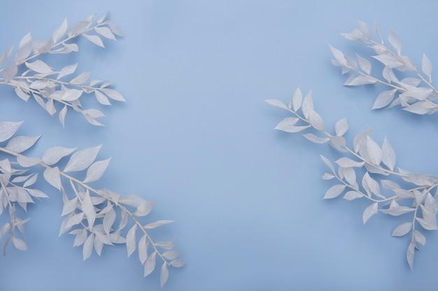 青いテーブルの葉と白い枝のフレーム