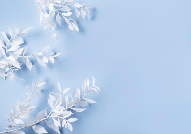 Рамка из белых веток с листьями на синей стене