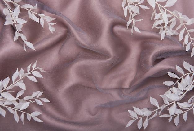 薄茶色の壁に葉を持つ白い枝のフレーム