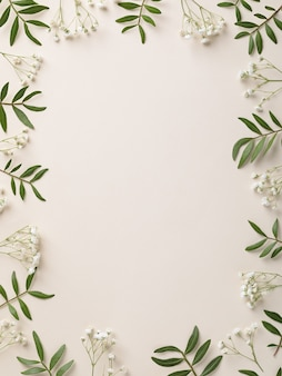 Рамка из белых цветов и зеленых листьев на белом фоне biege
