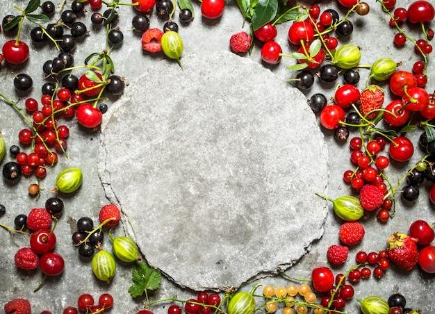 Рамка из лесных ягод со свободным местом для текста. на каменном столе.