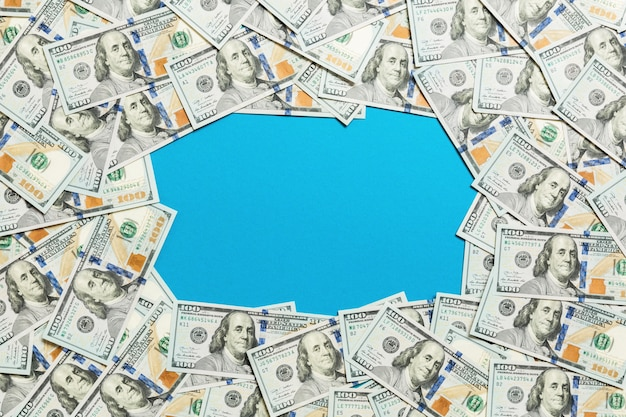 Frame of one hundred dollar bills . top view of business  on blue  with copyspace
