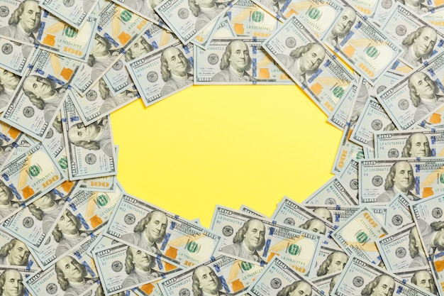 Frame of one hundred dollar bills. top view of business concept on yellow background