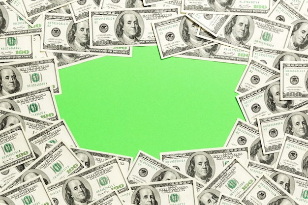 Frame of one hundred dollar bills with empty space r . top view of business  on green  with copyspace