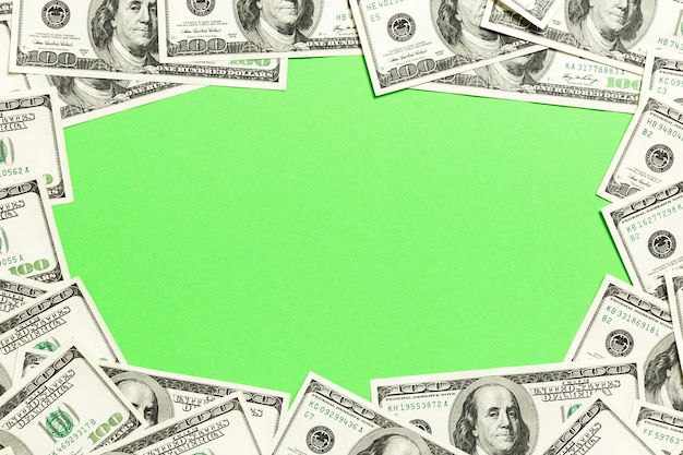 Frame of one hundred dollar bills with empty space for your design. top view of business concept on green background with copy space.