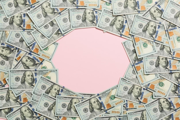 Frame of one hundred dollar bills with empty space for your design. top view of business concept on pink background with copy space.