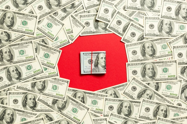 Frame of one hundred dollar bills with stack of money in the middle. top view of business concept on red background with copy space.