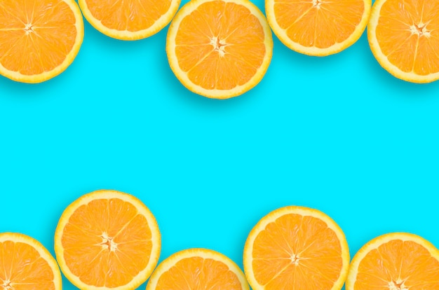 Frame of an orange citrus slices on bright blue background