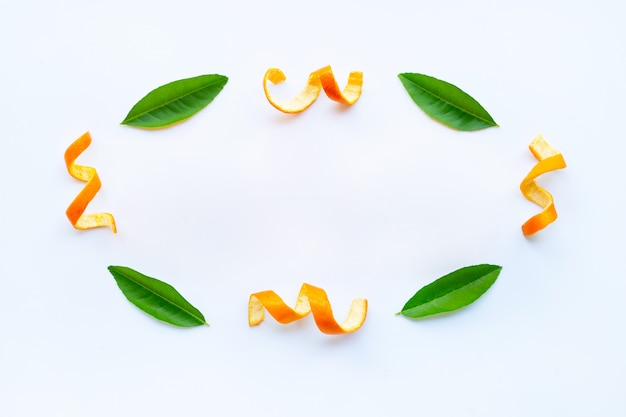 Frame of orange peels with green  leaves on white