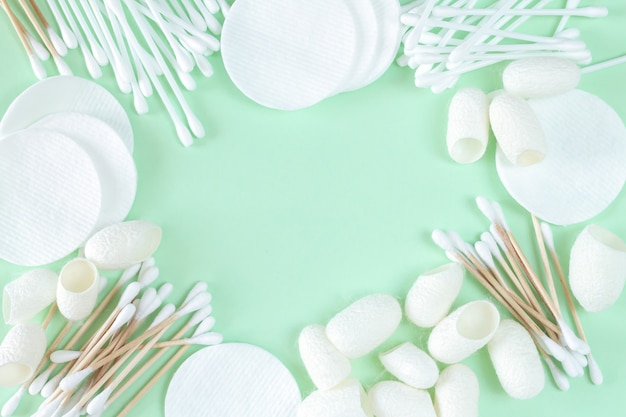 Frame of organic cotton cosmetic removers and skin care products: pads, cotton swabs, silkworm cocoons top view