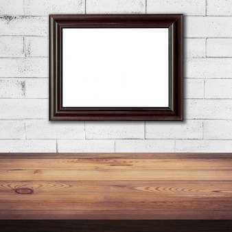 Frame picture on white brick wall and wood table background texture with space