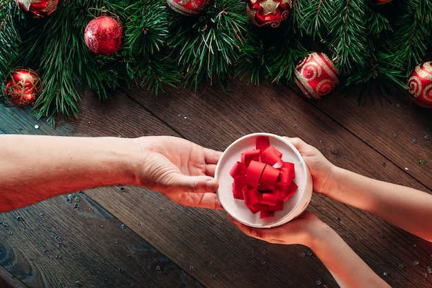A frame of pine branches and christmas decorations and hands giving a gift on the  of a wooden table. merry christmas and happy holidays. view from above.
