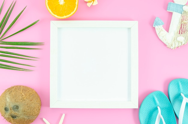 Frame on pink background with tropical leafs, coconut, orange,slippers