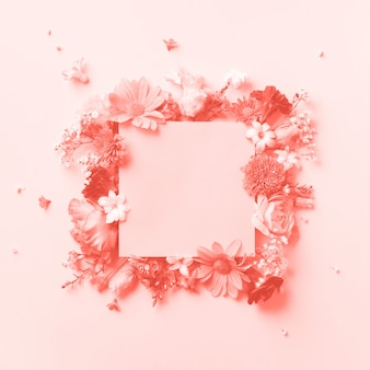 Frame of pink flowers over coral color background.