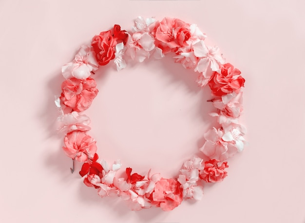 Frame of pink flowers over a pink background  top view