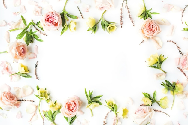 Frame of pink roses, branches, leaves and petals isolated