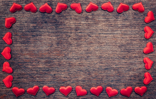 Frame of red heart on wooden background with copyspace.