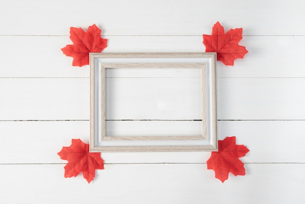 Frame and red maple leaves on white wooden background. autumn, fall , top view, copy space.