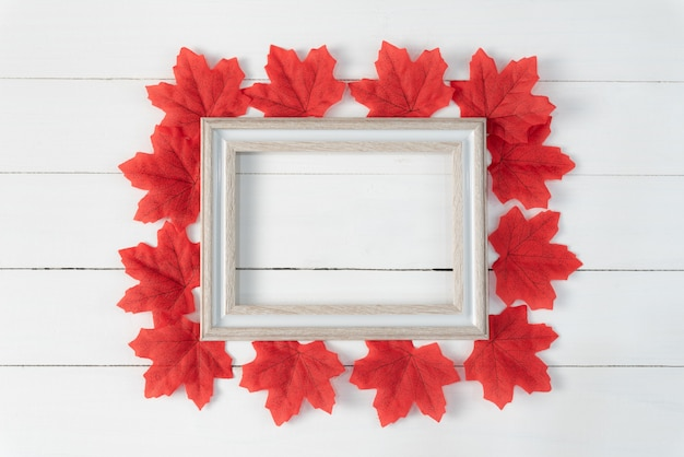 Frame and red maple leaves on white wooden background