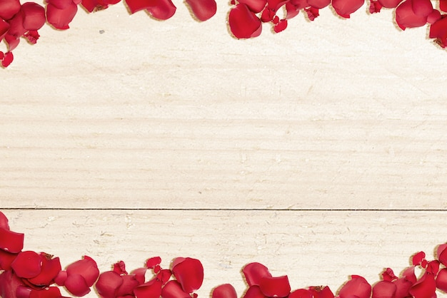 The frame of red rose petals with a wooden table background