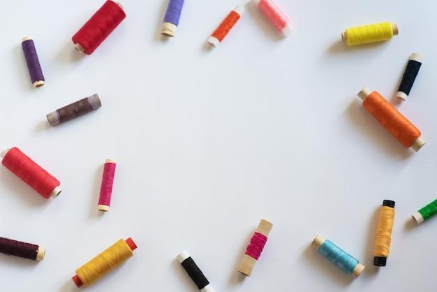 Рамка. катушки с нитками разных цветов и размеров на белом фоне. плоская планировка. место для текста