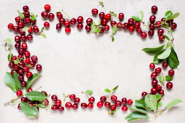 Frame of ripe red cherries on the textured gray table