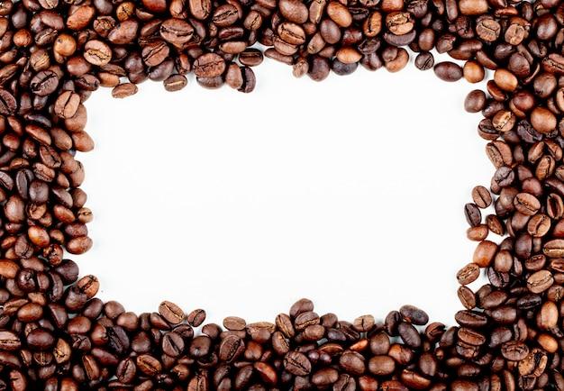 Pagina dei chicchi di caffè arrostiti sulla vista superiore del fondo bianco