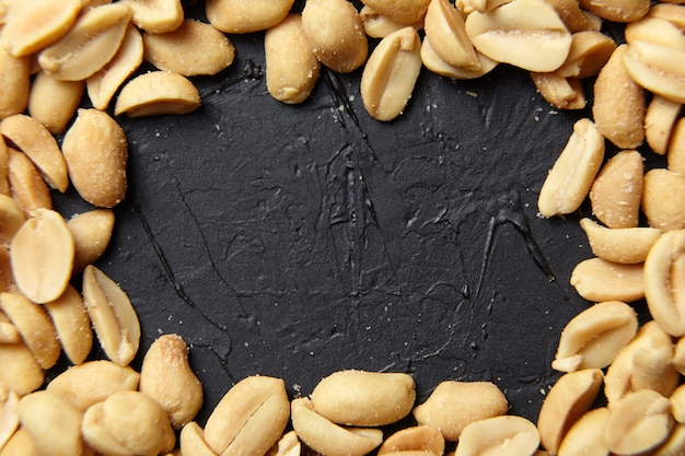 Frame of roasted peeled peanuts closeup, salty beer snack on black background