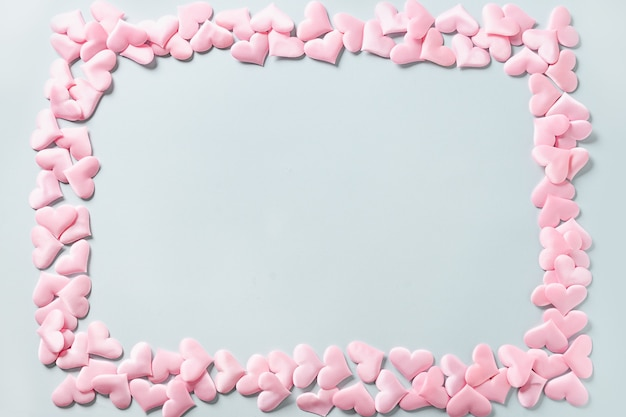 Frame of romantic pink hearts on blue background. valentine's day greeting card with copy space. love concept.
