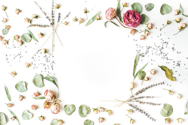 Frame of roses, lavender, branches, leaves and petals